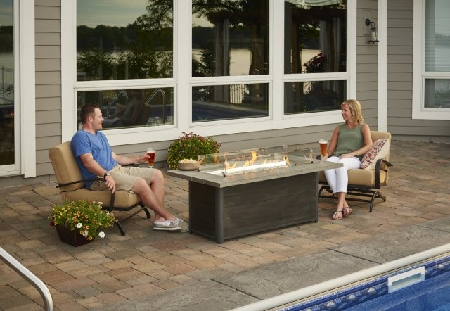 Couple sitting together in front of a Cedar Ridge Gas Fire Pit Table made by The Outdoor GreatRoom Company.
