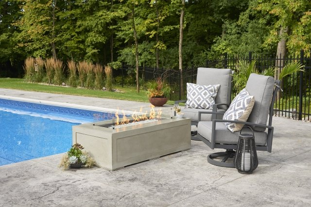 natural, contemporary look Cove 1242 Gas Fire Pit Table with Glass Wind Guard by The Outdoor GreatRoom Company for your patio or poolside theme