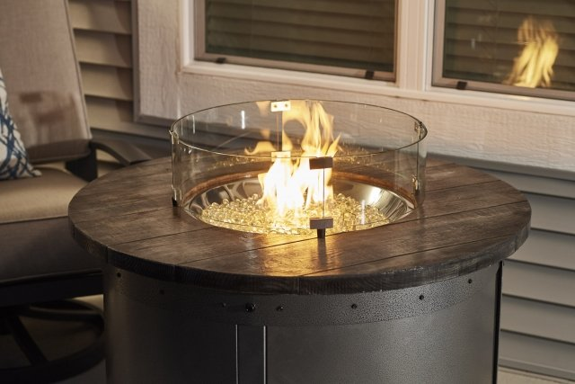 Modern, industrial design Edison Round Gas Fire Pit Table with Glass Guard by The Outdoor GreatRoom Company for your patio or porch