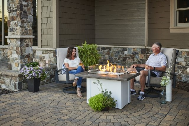 People sitting in front of their home and enjoying the Havenwood Gas Fire Pit Table made by the Outdoor Greatroom Company.