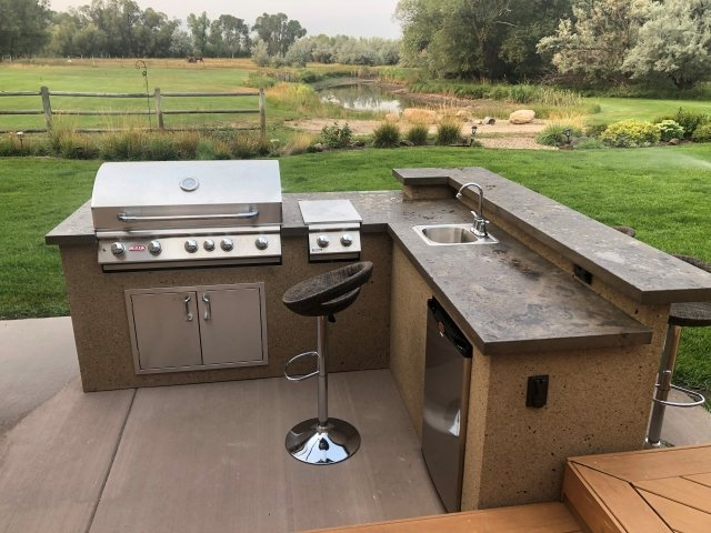 Outdoor kitchen in a backyard with grass in the background.