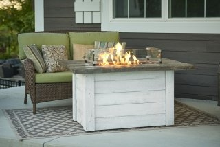 Farmhouse, distressed design Alcott Gas Fire Pit Table with Glass Wind Guard by The Outdoor GreatRoom Company for your modern patio or porch