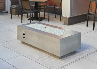 "Cove 54"" Linear Gas Fire Pit with no flame and optional stainless steel trim overlay rested on top of fire pit"