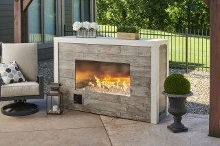Forty-inch ready-to-finish single-sided fireplace with beautiful flame and outdoor accessories staged around it